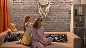 Little daughter brushing her mother hair with hairbrush, sitting on sofa in modern living room, family concept indoors stock footage