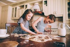 The little daughter in the chef`s hat and apron and her mother prepare baking in the bright, classic kitchen. Mothers Day royalty free stock images
