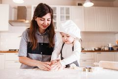 The little daughter in the chef`s hat and apron and her mother prepare baking in the bright, classic kitchen. Mothers Day stock image