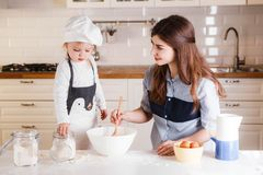 The little daughter in the chef`s hat and apron and her mother prepare baking in the bright, classic kitchen. Mothers Day stock photography