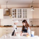 The little daughter in the chef`s hat and apron and her mother prepare baking in the bright, classic kitchen. Mothers Day royalty free stock photos