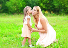 Little daughter child kissing loving mother in summer day, happy family Royalty Free Stock Photo