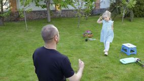 Little daughter come to father in the garden stock footage