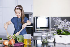 Little daughter cooking in the kitchen Royalty Free Stock Photo