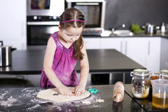 Little daughter cooking in the kitchen Stock Photos