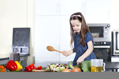 Little daughter cooking in the kitchen Stock Image