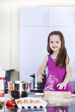 Little daughter cooking in the kitchen Royalty Free Stock Images