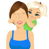Little daughter covering her happy mother eyes Stock Photos