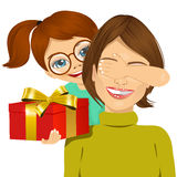 Little daughter covering mother eyes with her hand. Little daughter with glasses standing behind mother covering her eyes with her hand while giving a present Royalty Free Stock Photography