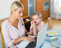 Little daughter diverts mother from work Royalty Free Stock Photography