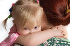Little daughter embraces mum for a neck. Royalty Free Stock Images
