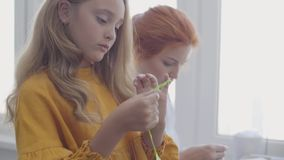 Little daughter examines sewing accessories and learning how to sew while her red-haired mother sews clothes sitting at