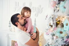 Little daughter and father near Christmas tree. Happy New Year.  Royalty Free Stock Photo