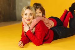 Little daughter five year old with her young mom. Little girl lay on my mother`s back. Yellow background royalty free stock photo
