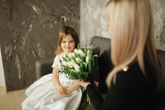 Little daughter give to mother bouquet of flowers. Mom and daughter at home. Bouquet of flowers on 8th of march.  stock image