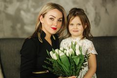 Little daughter give to mother bouquet of flowers. Mom and daughter at home. Bouquet of flowers on 8th of march.  royalty free stock photos