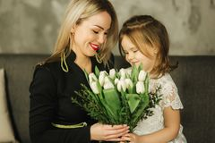 Little daughter give to mother bouquet of flowers. Mom and daughter at home. Bouquet of flowers on 8th of march.  royalty free stock photography