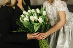 Little daughter give to mother bouquet of flowers. Mom and daughter at home. Bouquet of flowers on 8th of march.  royalty free stock image