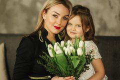Little daughter give to mother bouquet of flowers. Mom and daughter at home. Bouquet of flowers on 8th of march.  royalty free stock images
