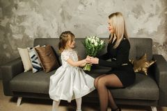Little daughter give to mother bouquet of flowers. Mom and daughter at home. Bouquet of flowers on 8th of march.  stock photography
