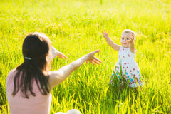 Little daughter happily running towards her mom Stock Photo
