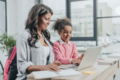 Little daughter helping mother working on laptop at business office Stock Photo
