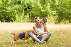 Daughter and her mother are smiling while posing with their pets royalty free stock images