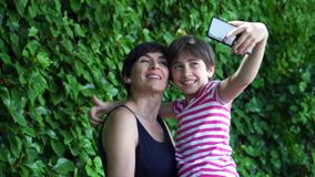 Little daughter and her mother taking selfie photo. Little daughter and her mother taking selfie photo with smart phone stock video footage