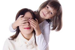 Little daughter hiding mothers eyes Stock Images