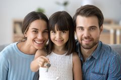 Little daughter holding keys happy family buy new home. Head shot happy diverse family sitting on couch at new home. Young married couple wife and husband their stock images