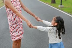 Little daughter holding mother hands in the outdoor nature garden royalty free stock images