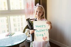 Little daughter holding painted postcard and bouquet of flowers for mom. Happy Mother day concept royalty free stock image