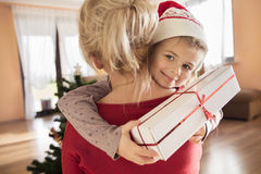 Little daughter hugging her mum holding a gift stock photo