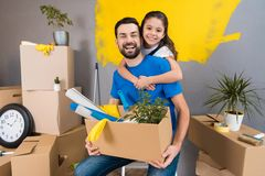 Little daughter hugs her father, who keeps box of tools and things. Family does house repairs together. Overhaul of house stock photos