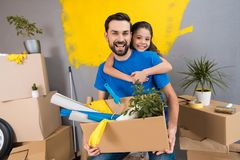 Little daughter hugs her father, who keeps box of tools and things. Family does house repairs together. Overhaul of house stock photo