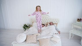 Little daughter jumping and fooling in bed while parents sleeping. stock image
