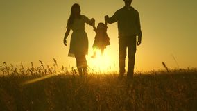 Little daughter jumping holding hands of dad and mom in park on background of sun. Family concept. child plays with dad stock footage