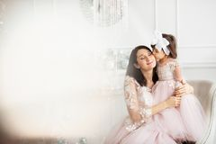 The little daughter kisses her mother. Mom and daughter are dressed in beautiful dresses royalty free stock images