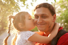 Little daughter kissing father. Happy family outdoors. Stock Image