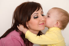 Little daughter kissing her mother. Stock Image