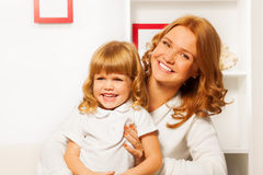 Little daughter with mother at home Stock Images