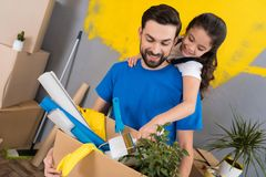 Little daughter with paintbrush hugs father, who keeps box of tools and things. Family does house repairs together. Moving to new apartment royalty free stock photos