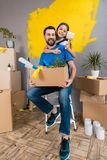 Little daughter with paintbrush hugs father, who keeps box of tools and things. stock images