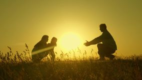 Little daughter with parents jumping at sunset. Silhouettes of mom dad and baby in the rays of dawn. Family concept. Walking with a small child in nature stock photos