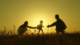 Little daughter with parents jumping at sunset. Silhouettes of mom dad and baby in the rays of dawn. Family concept. Walking with a small child in nature royalty free stock photo