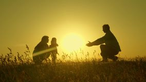 Little daughter with parents jumping at sunset. Silhouettes of mom dad and baby in the rays of dawn. Family concept. Walking with a small child in nature royalty free stock images