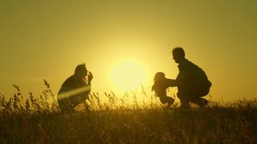 Little daughter with parents jumping at sunset. Silhouettes of mom dad and baby in the rays of dawn. Family concept. Walking with a small child in nature stock image
