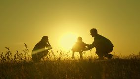 Little daughter with parents jumping at sunset. Silhouettes of mom dad and baby in the rays of dawn. Family concept. Walking with a small child in nature stock images