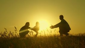 Little daughter with parents jumping at sunset. Silhouettes of mom dad and baby in the rays of dawn. Family concept. Walking with a small child in nature royalty free stock photos