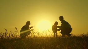 Little daughter with parents jumping at sunset. Silhouettes of mom dad and baby in the rays of dawn. Family concept. Walking with a small child in nature royalty free stock image